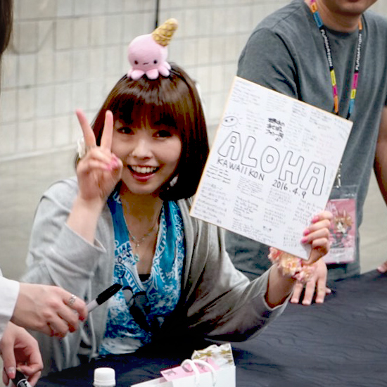 Shimoda poses with shikishi given to her by fans